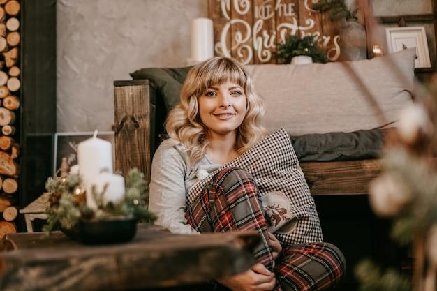 Jovem e bela mulher de pijama perto da lareira decorativa - clima de natal