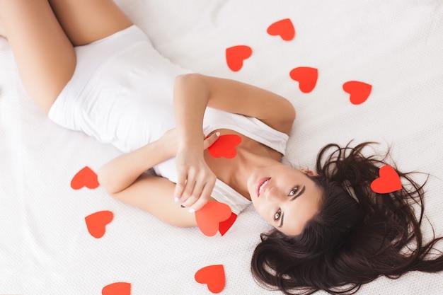 Jovem e bela mulher deitada na cama em lençóis brancos. mulher atraente com o coração do dia dos namorados. menina dentro de casa se divertindo.
