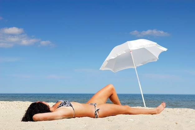 Jovem e bela mulher deitada na praia