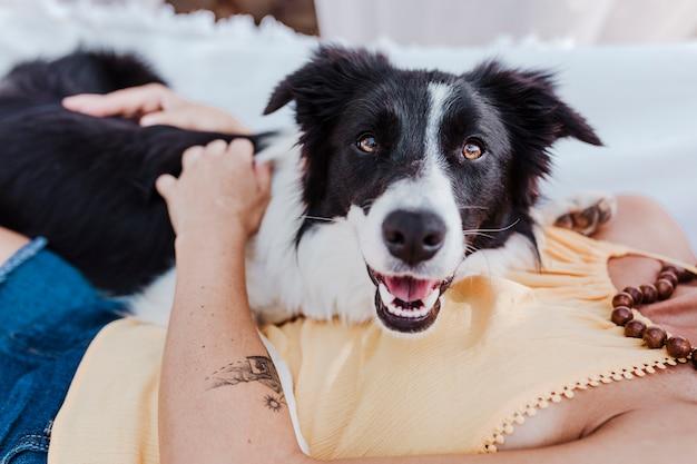 Jovem e bela mulher deitada na rede com seu cachorro border collie ao ar livre