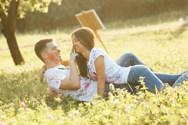 Jovem e bela mulher deitada no namorado vestindo camiseta colorida. casal muito alegre, sorrindo um para o outro ao ar livre