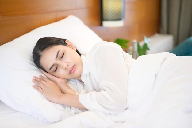 Jovem e bela mulher dormindo em sua cama em casa.