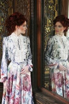 Jovem e bela mulher em pé na sala do palácio com espelho.