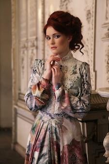 Jovem e bela mulher em pé na sala do palácio.