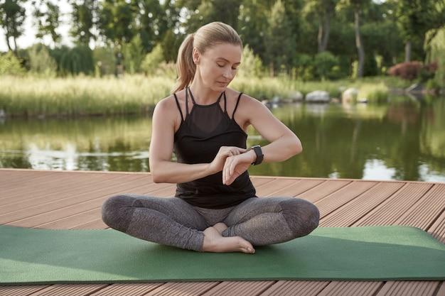 Jovem e bela mulher esportiva em roupas esportivas, sentada em posição de lótus no tapete de ioga e olhando para