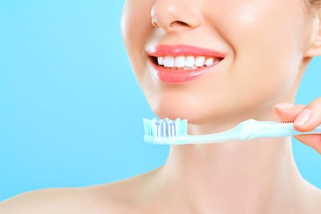 Jovem e bela mulher está envolvida em limpar os dentes. dentes brancos saudáveis de sorriso lindo. uma garota segura uma escova de dentes. o conceito de higiene oral.