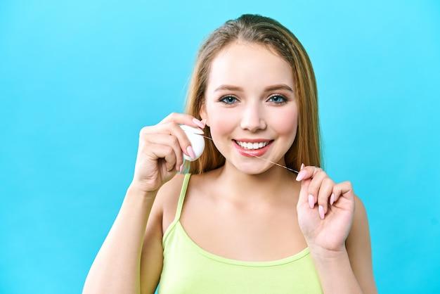 Jovem e bela mulher está envolvida em limpar os dentes.