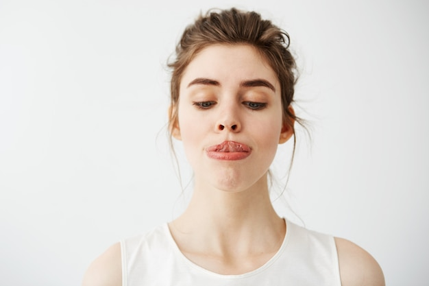 Jovem e bela mulher esticando a língua para o nariz.