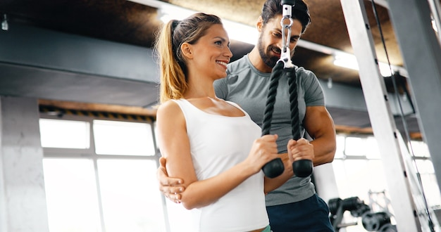 Jovem e bela mulher fazendo exercícios com o personal trainer na academia