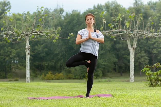 Jovem e bela mulher fazendo exercícios de ioga ao ar livre