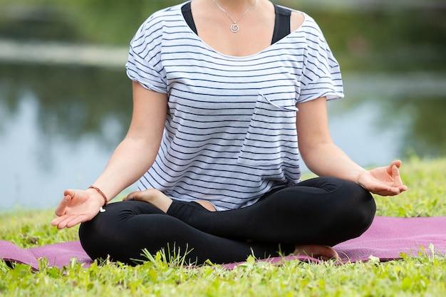 Jovem e bela mulher fazendo exercícios de ioga no parque verde. estilo de vida saudável e conceito de aptidão.