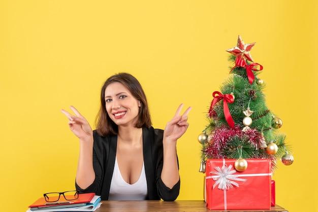 Jovem e bela mulher fazendo gesto de vitória sentada em uma mesa perto da árvore de natal decorada no escritório em amarelo