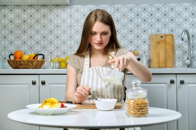 Jovem e bela mulher fazendo salada de frutas na cozinha com maçã, laranja, iogurte, flocos de milho e sementes. alimentação saudável cozinhada em casa, beleza e saúde dos jovens