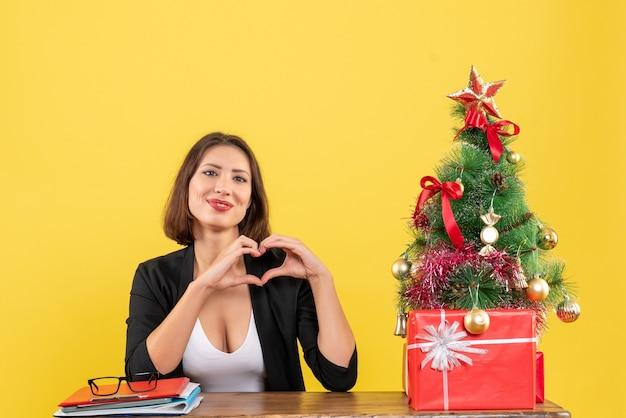 Jovem e bela mulher fazendo um gesto com o coração, sentada em uma mesa perto da árvore de natal decorada no escritório em amarelo