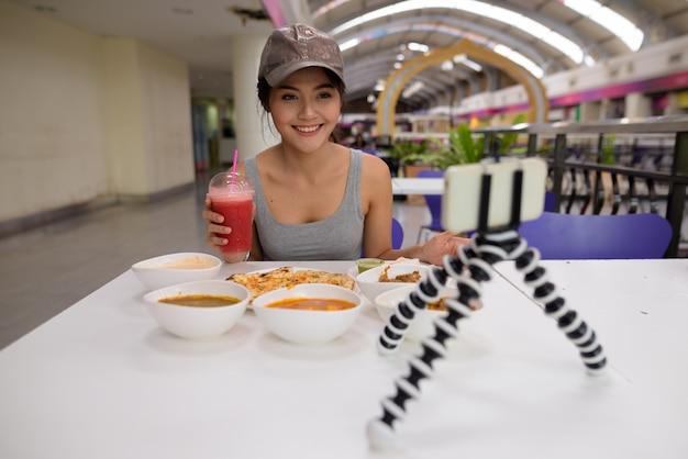 Jovem e bela mulher fazendo vlogs com celular em restaurante