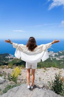 Jovem e bela mulher fica de costas e olha para a cidade velha de budva, montenegro.