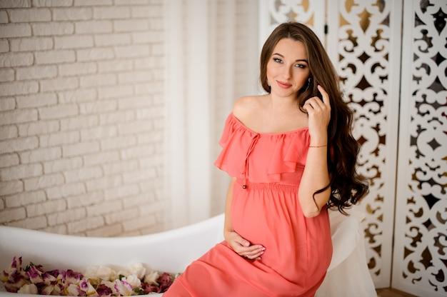 Jovem e bela mulher grávida em vestido longo