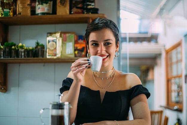 Jovem e bela mulher latina feliz tomando café em um café de rua