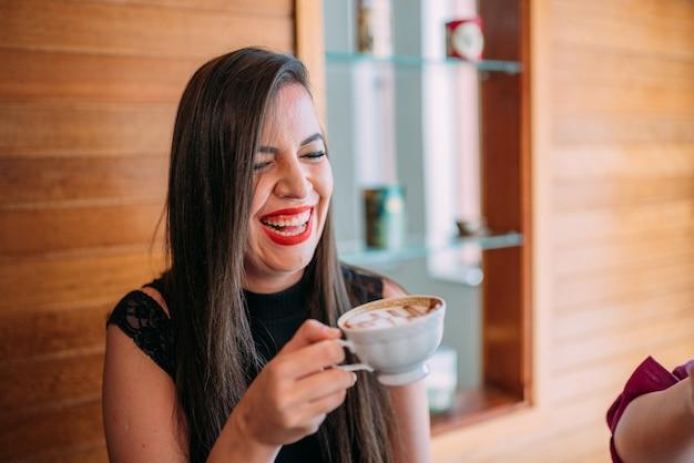 Jovem e bela mulher latina feliz tomando cappuccino em um café de rua