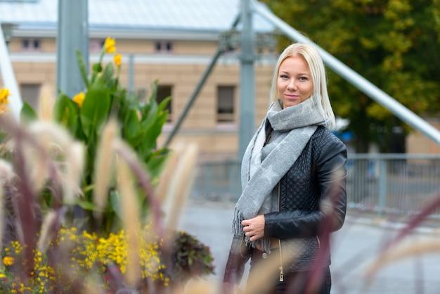 Jovem e bela mulher loira contra um prédio urbano de tijolos com arbustos floridos e plantas perenes