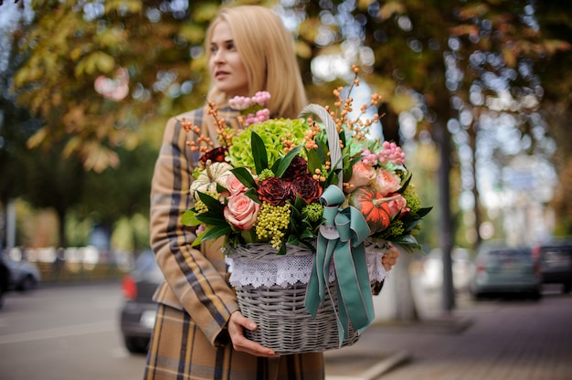 Jovem e bela mulher loira segurando uma cesta de vime grande de flores contra a cidade