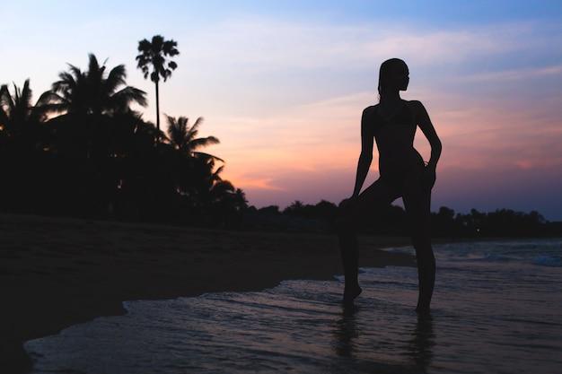 Jovem e bela mulher magra em pé na praia ao amanhecer, férias tropicais, palmeiras, silhueta, sexy, sensual, ondas do mar, céu colorido