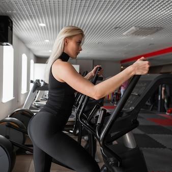 Jovem e bela mulher magra fazendo treinamento cardiovascular em um simulador de passo em uma academia moderna