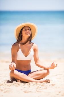 Jovem e bela mulher meditando na praia perto do mar
