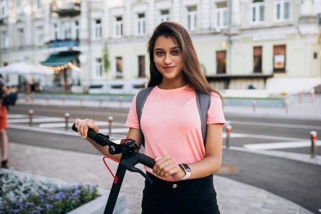 Jovem e bela mulher montando uma scooter elétrica, garota moderna no transporte ecológico.