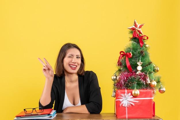 Jovem e bela mulher mordendo a língua mostrando dois sentados em uma mesa perto da árvore de natal decorada no escritório em amarelo