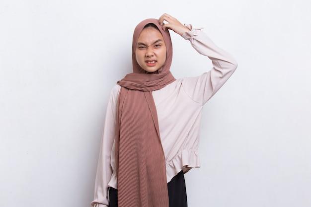Jovem e bela mulher muçulmana asiática coçando a cabeça com a mão isolada no fundo branco
