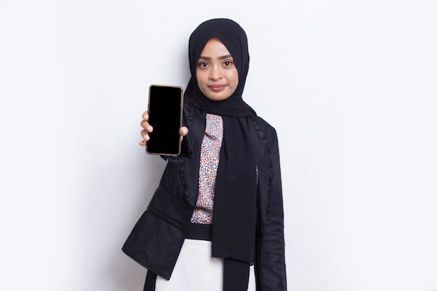 Jovem e bela mulher muçulmana asiática demonstrando telefone celular isolado no fundo branco