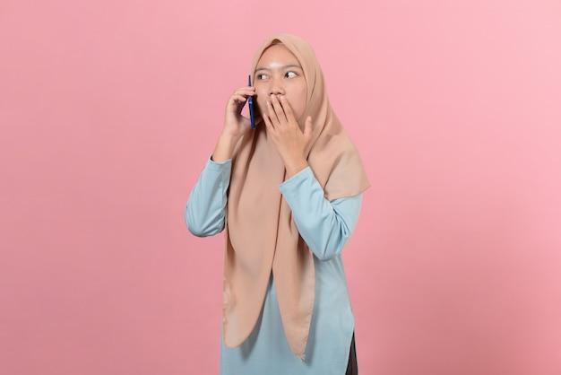Jovem e bela mulher muçulmana asiática surpresa chocada com o celular fechar a boca com a palma da mão, isolado em um fundo rosa