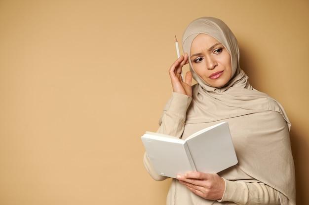 Jovem e bela mulher muçulmana em hijab olhando para o lado com um olhar pensativo segurando um bloco de notas branco e um lápis em sua têmpora