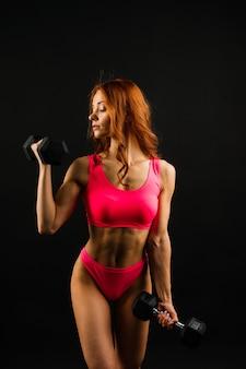 Jovem e bela mulher musculosa, desportiva, isolada contra um fundo branco e preto