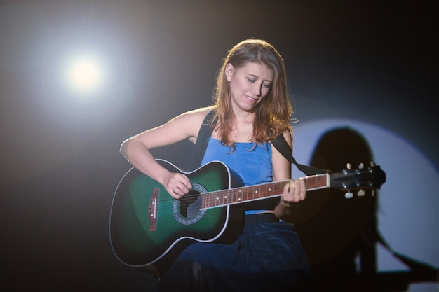 Jovem e bela mulher no palco sob os holofotes tocando violão e cantando canções folclóricas em estilo country