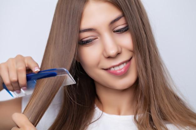 Jovem e bela mulher penteando o cabelo na sala de estar.