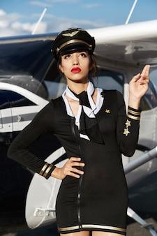 Jovem e bela mulher piloto ou aeromoça na frente do avião, segure os dedos para dar sorte