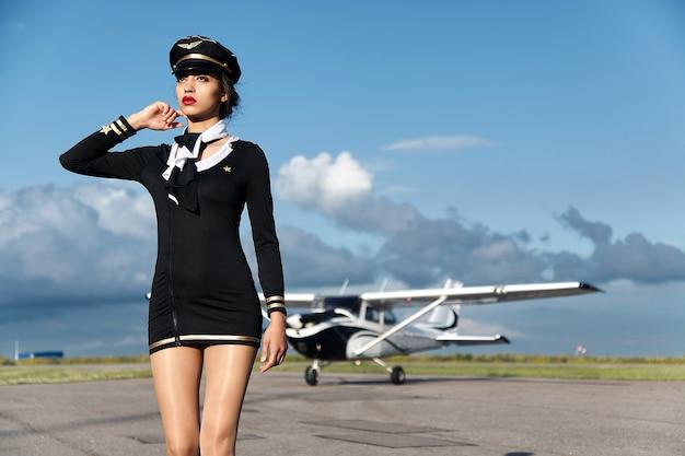 Jovem e bela mulher piloto ou aeromoça na frente do avião.