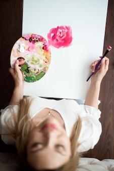 Jovem e bela mulher pintando em casa peônias cor de rosa