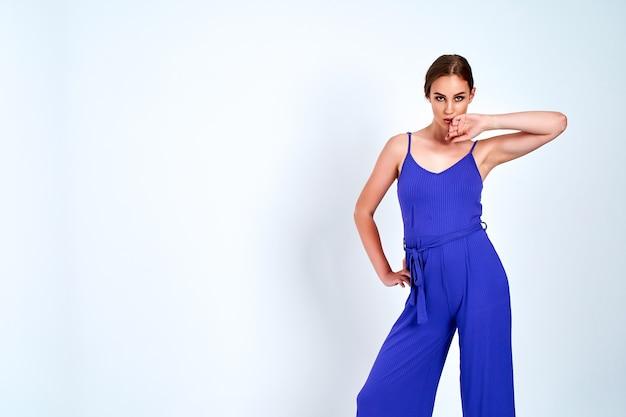 Jovem e bela mulher posando com um novo traje de moda casual azul vestido com calças de corpo inteiro em fundo branco