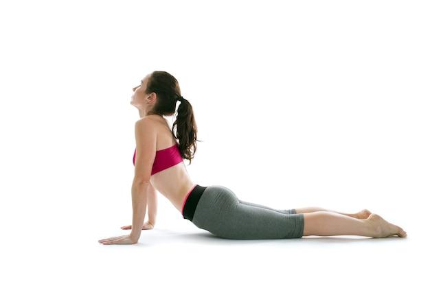 Jovem e bela mulher posando de ioga em um fundo branco