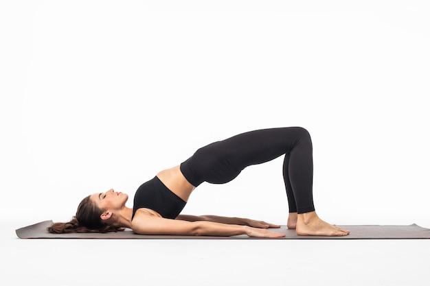 Jovem e bela mulher posando de ioga isolada sobre a superfície branca do estúdio