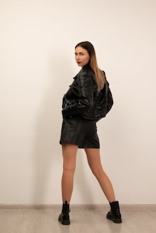 Jovem e bela mulher posando no estúdio em shorts de couro preto, botas e jaqueta