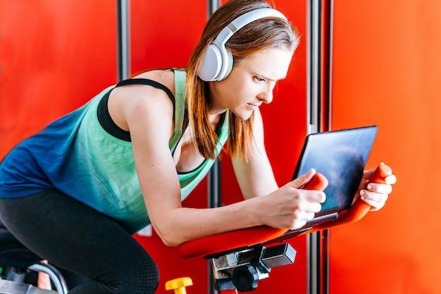 Jovem e bela mulher praticando esportes com fones de ouvido musicais, olhando para a tela de um laptop