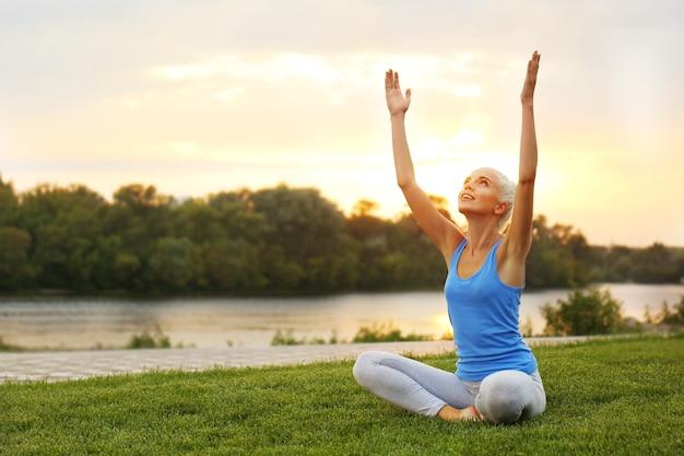 Jovem e bela mulher praticando ioga na grama perto do lago
