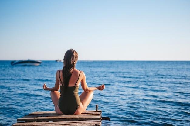 Jovem e bela mulher praticando ioga na praia