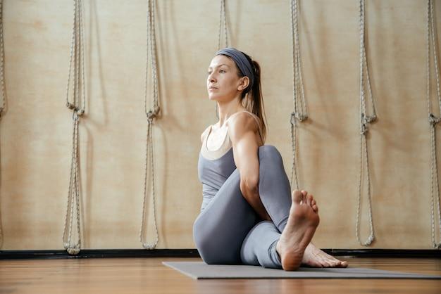 Jovem e bela mulher praticando ioga no estúdio de ioga. harmonia, equilíbrio, meditação, relaxamento, conceito de estilo de vida saudável