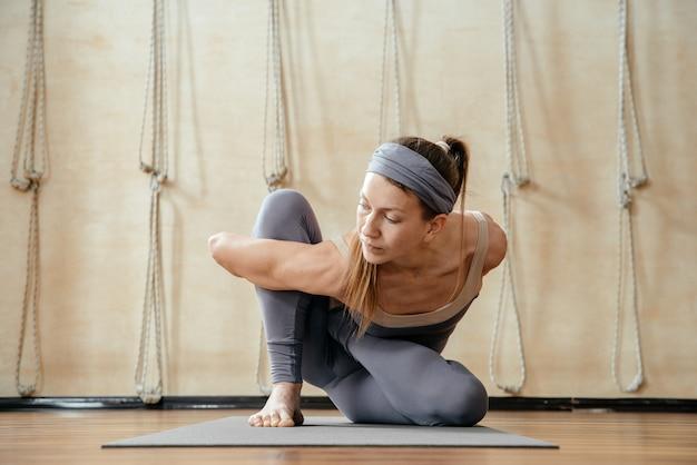 Jovem e bela mulher praticando ioga no estúdio de ioga. harmonia, equilíbrio, meditação, relaxamento