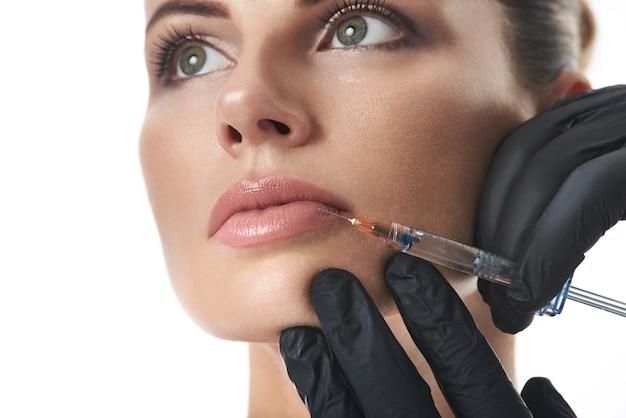 Jovem e bela mulher recebendo injeção de preenchimento nos lábios. cosmetologia de injeção